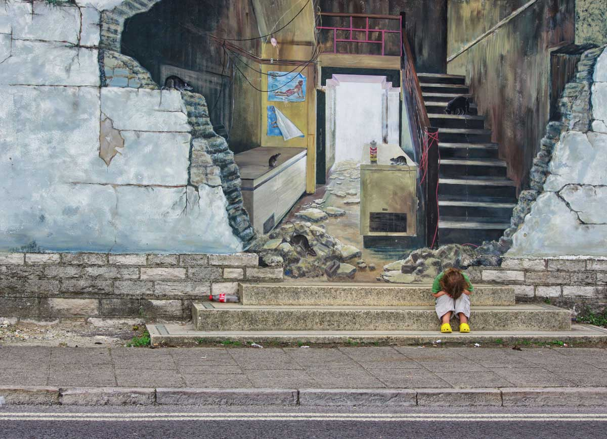 Child in a temper on the steps next to graffiti